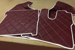 Set of faux leather floor mats in maroon with white trim. Diamond quilting as requested by customer.